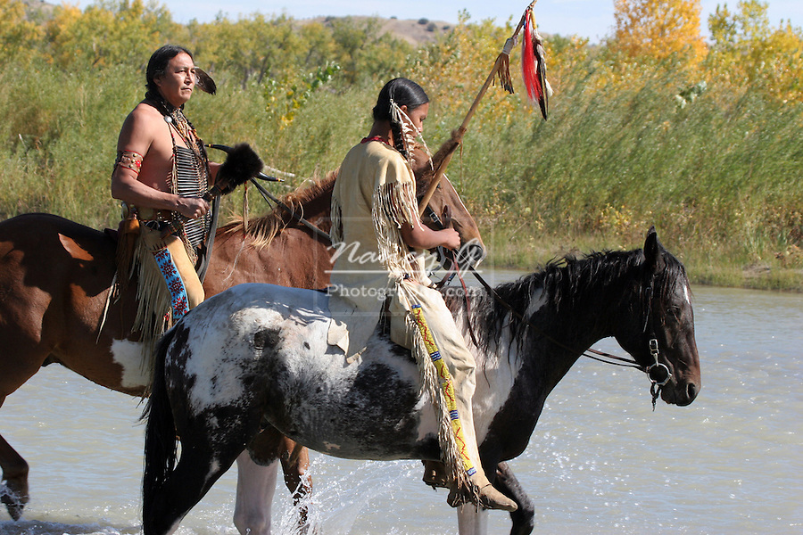 Two Native American Sioux Indian men on horseback walking through a river