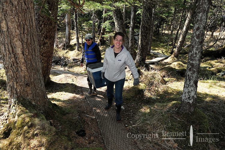 Georgia Bennett, left, and Renee Huntman carry a cooler up the path to Decision Cabin, in Decision Point State Marine Park, in Squirrel Cove, off Passage Canal, Prince William Sound, Southcentral Alaska, near Whitter, on a sunny spring afternoon in mid-May. MR