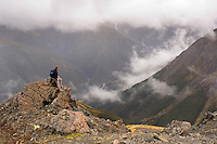 Hiker looking down on cloudy valley in Arthur's Pass National Park, New Zealand
