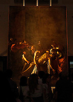 """Alcune persone osservano il quadro del Caravaggio """"Resurrezione di Lazzaro"""" appena restaurato ed in mostra al Museo di Roma Palazzo Braschi..15 giugno 2012..Dipinto dal Caravaggio in Sicilia nel 1609, il quadro, proveniente dalla Chiesa dei Padri Crociferi di Messina, è stato restaurato a Roma dall' ISCR, Istituto Superiore per la Coservazione e Restauro, struttura del Mibac, in accordo con il Museo Regionale di Messina..People look at the restored Caravaggio's """"Resurrection of Lazarus"""" at the Palazzo Braschi Museum in Rome, 15 June 2012..Painted by Caravaggio in Sicily in 1609, the painting was restored in Rome by experts of the Higher Institute for Conservation and Restoration (ISCR) in accordance with the Regional Museum of Messina..UPDATE IMAGES PRESS/Isabella Bonotto"""