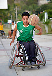 Alejandro Jarquin dribbles the basketball while pushing his wheelchair forward during practice in Zipolite, a town in Oaxaca, Mexico. Jarquin plays on the Oaxaca Costa wheelchair basketball team.