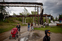 People walk along a track beneath heating pipes in the village of Lopcha. The village was founded in 1978 during the construction of the Baikal Amur Magistral (BAM) railway line. The village now has a population of 500.