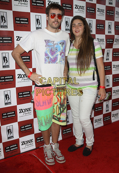 """PABLO LARCUEN & GUEST.2010 Los Angeles Film Festival Opening night premiere """"The Kids Are All Right"""" held at Regal Cinemas, Los Angeles, CA, USA..June 17th, 2010.full length pink green shorts white t-shirt jeans denim striped stripes sunglasses shades hand on hip .CAP/ADM/KB.©Kevan Brooks/AdMedia/Capital Pictures."""