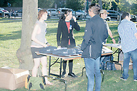 """People gather around a campaign table before entrepreneur and Democratic presidential candidate Andrew Yang speaks to a large crowd in Cambridge Common near Harvard Square in Cambridge, Massachusetts, on Mon., September 16, 2019. Yang's unlikely presidential bid is centered on his idea for a """"Freedom dividend,"""" which would give USD$1000 per month to every adult in the United States. After appearing in three Democratic party debates, Yang has risen in polls from longshot candidate to within the top 10."""