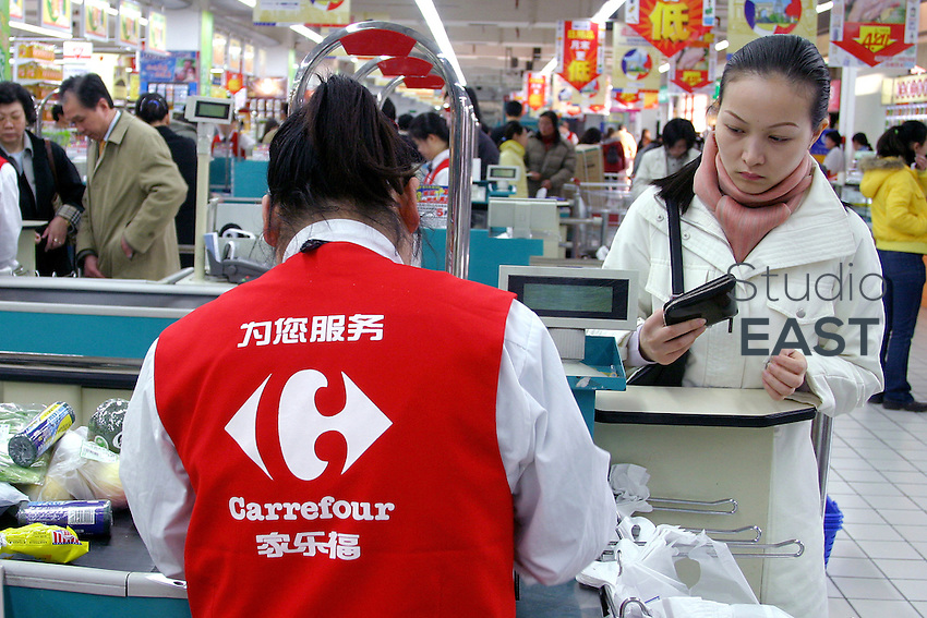"""A cashier counts a customer's purchases in Carrefour supermarket in Shanghai, China, on March 24, 2005. Some Chinese Internet users have launched a boycott of French products, in order to protest against the way the Olympic torch was handled when in Paris. A short text message is circulating between Chinese users, saying """"Let's not buy anything at Carrefour's. Let's boycott Carrefour at least until the Olympics"""". Photo by Eric Leleu/Pictobank"""