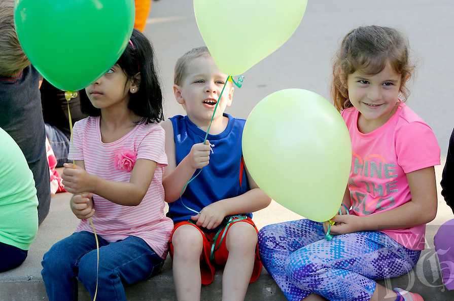 NWA Democrat-Gazette/DAVID GOTTSCHALK  Kindergarten students Maryam Hashim (from left), Holden Miller and Presley Jackson hold onto their balloons before participating in a balloon release Friday, August 7, 2015 with thier class. Three classes of kindergarten students participated in the annual release marking the launch of their academic careers.