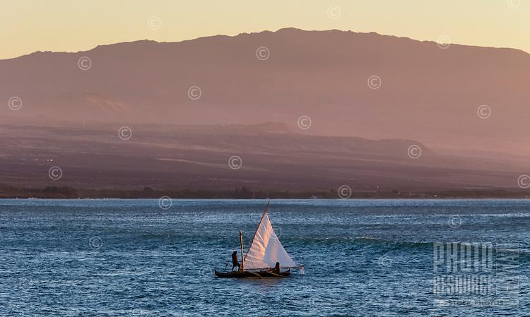 Canoe sailors hoist up their sail along the Big Island's Kohala Coast, with Hualalai Volcano looming in the distance.