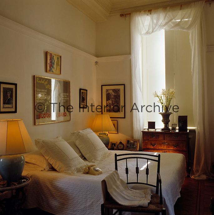 The walls of the bedroom are adorned with framed prints and the muslin drapes that frame the window accentuate the height of the ceiling