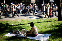 A woman sitting on the Commonwealth Avenue Mall in Back Bay watches as the OccupyBoston demonstration marches in Boston, Massachusetts, USA.  The protesters are part of  OccupyBoston, which is part of the OccupyWallStreet movement, expressing discontent with the socioeconomic situation of the 99% of the US population who are not wealthy.  Protestors have been camping in Dewey Square since Sept. 30, 2011. Gradually, larger organizations, including major labor unions, have expressed their support for the OccupyBoston effort.