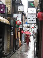 A Geisha walks through the rain under a red umbrella