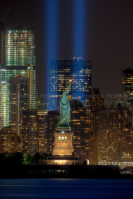 The twin beams of light of the Tribute in Light, an annual memorial to the events of September 11, 2001, shine into the evening sky in New York City on either side of the Statue of Liberty on Tuesday, September 11, 2012.