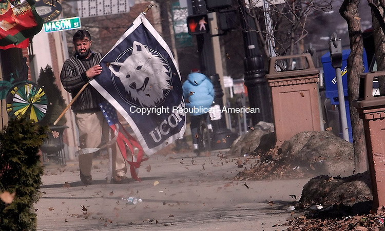 TORRINGTON, CT24 February 2006-022406TK04 Jorge Coelho of Scents and Sensibility on Main Street in Torrington removes his flag display from the front of his business due to the strong winds that dominated Friday's weather.   Tom Kabelka / Republican-American (Jorge Coelho)CQ