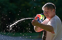 Father and son squirt each other with pump water guns during a friendly afternoon play session