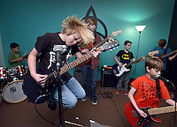 STAFF PHOTO BEN GOFF  @NWABenGoff -- 12/27/14 Henry Colebank, 10, of Fayetteville gets into the moment while rehearsing classic rock and metal tunes during the Rock 101 class at the School of Rock in Rogers on Saturday Dec. 27, 2014. The students are preparing for their next public performance, which will be during Last Night Fayetteville on December 31.