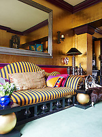 A long banquette upholstered in a striped fabric dominates one wall of the living room