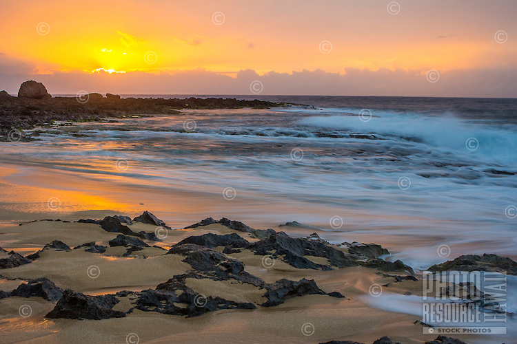 The sunset's glow reflects in the water receding along the shoreline at Ke Iki on the North Shore, O'ahu.