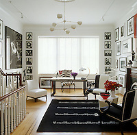An Eileen Gray Black Board rug is the centrepiece in this black-and-white themed living room where the walls are lined with photographs by David Bailey, Patrick McMillan, Willy Rizzo and Miles Aldridge