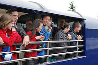 Passengers between two trains smile at one another as they pass by. The Alaska Railroad's Denali Star train runs between Anchorage and Fairbanks, with Denali one of the stops along the way.
