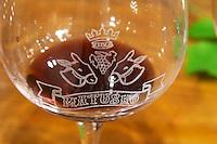 Wine Glass with emblazoned decoration of crown grape bunch two donkey's heads and the winery name. Matusko Winery. Potmje village, Dingac wine region, Peljesac peninsula. Matusko Winery. Dingac village and region. Peljesac peninsula. Dalmatian Coast, Croatia, Europe.