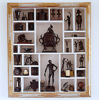 In the living room an antique gilded picture frame has been used as a surround for a built-in cabinet housing a collection of bronze figures