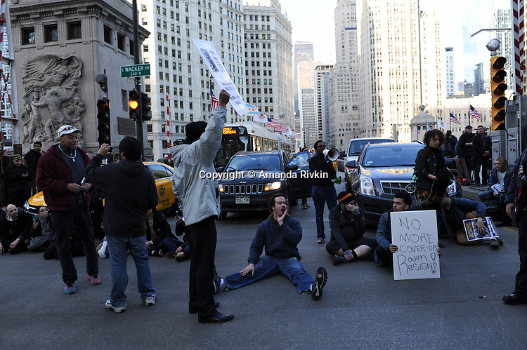 Protesters calling on Chicago Mayor Rahm Emanuel to resign stage a sit in and block traffic on Michigan Avenue at Wacker Drive in the Loop in Chicago, Illinois on December 9, 2015.  Emanuel offered a historic apology for the police killing of Laquan McDonald and police brutality and racial profiling generally -- without using those words -- in front of the City Council in the morning.
