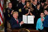 United States President Donald J. Trump holds up a signed Presidential Memorandum declaring the opioid crisis a national health emergency in the East Room of the White House on Thursday October 26th, 2017 in Washington, D.C.   First lady Melania Trump looks on from upper center.<br /> Credit: Alex Edelman / CNP