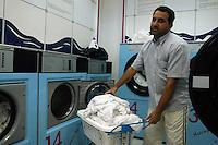Immigrato lavora in una lavanderia a gettoni..Immigrant works in a laundromat....