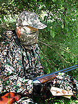 Wild turkey hunter in full camouflage with face mask.