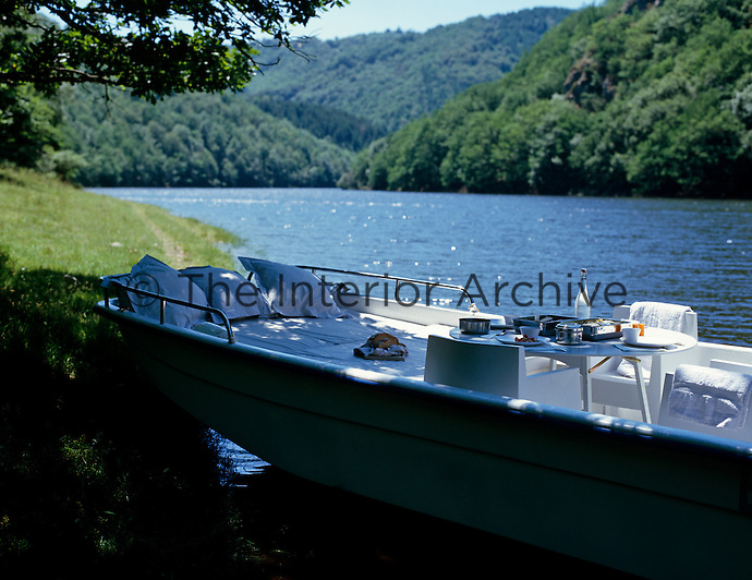 A boat is moored on the riverbank and an al fresco lunch is laid out on a table on board