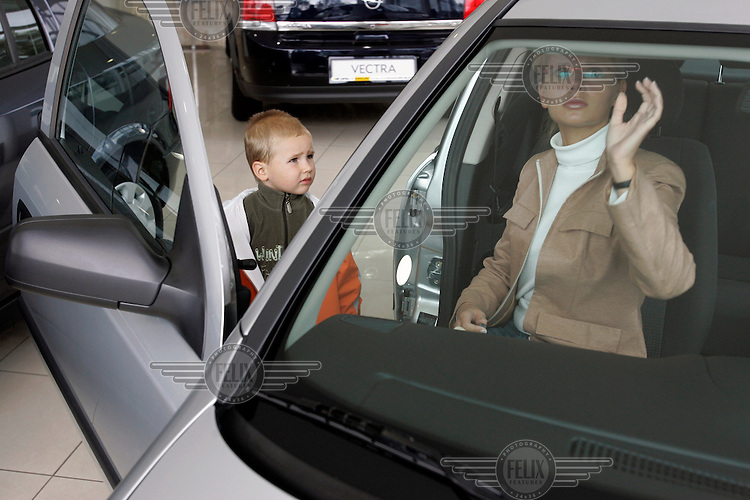 A mother and her young son inspect an Opel (Vauxhall) Astra car on sale at the Opel Kanclerz dealership. The cars sold by the dealer are manufactured at the local General Motors (GM) car plant.