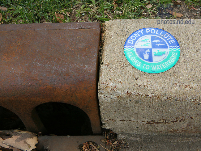 "Signs next to storm drains say ""Don't pollute, flows to waterways."".For Notre Dame Magazine"