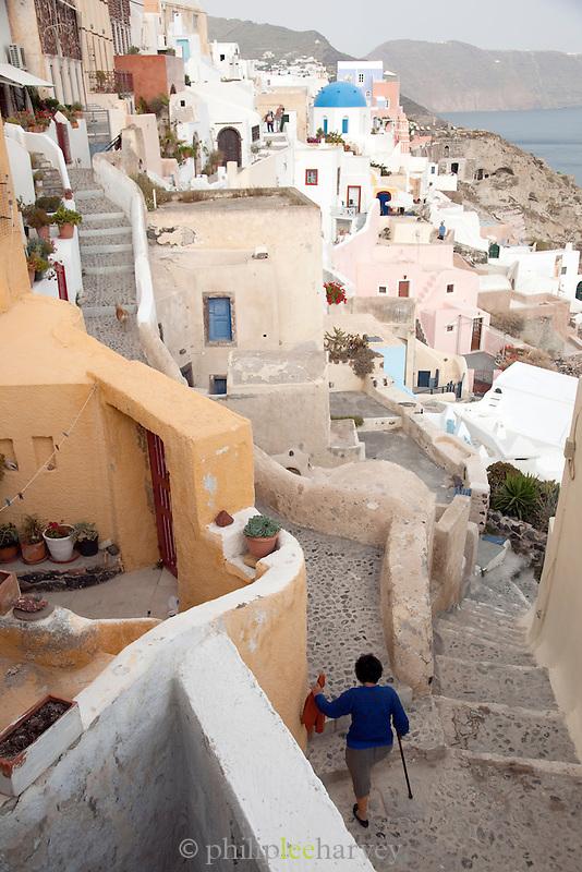 Woman walking up the steps in Oia, Santorini, Greece