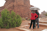 Asian couple with umbrella in Arches National Park, Moab, Utah, USA. .  John offers private photo tours in Arches National Park and throughout Utah and Colorado. Year-round.