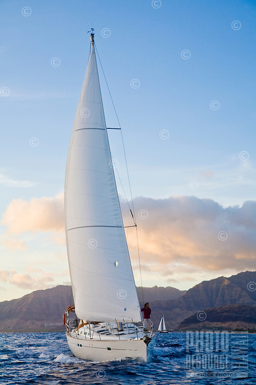 Cruising sailboat off the west coast of Oahu, Hawaii, with Waianae Mountain Range in the background