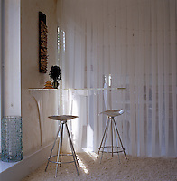 The small wall-mounted perspex bar is designed by Noriega-Ortiz and the stools are by Saarinen