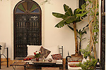 A patio with a table and chairs and palm trees in Marrakesh, Morocco.