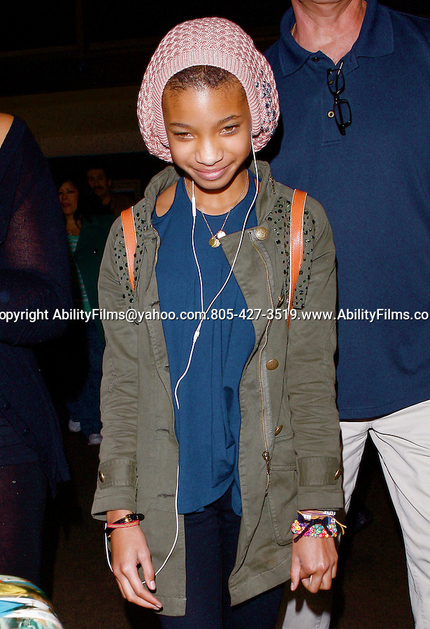 AbilityFilms@yahoo.com.805-427-3519.www.AbilityFilms.com..Feb 14th 2012..Willow Smith smiling as she comes through the LAX Los Angeles airport with her new shaved head.  Willow was wearing pink beanie listening to music on her ipod in a green army jacket ...