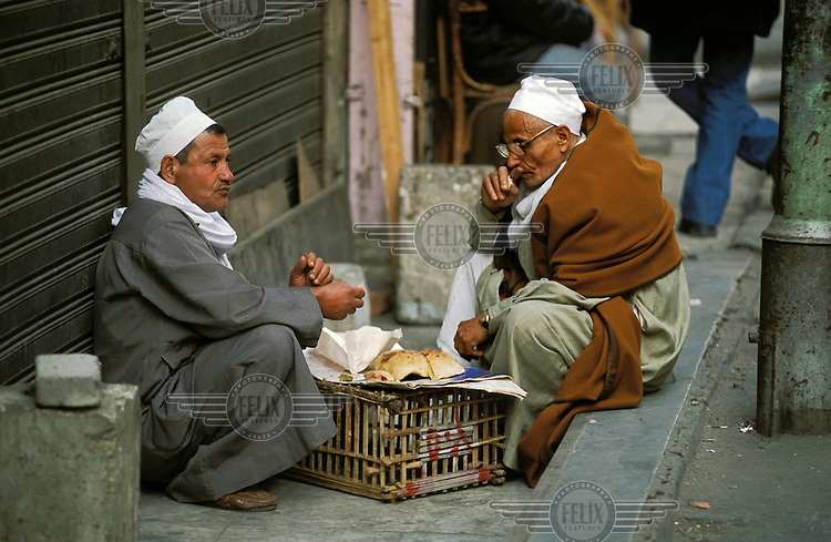 Men wearing traditional clothing eating lunch together on a downtown pavement. .