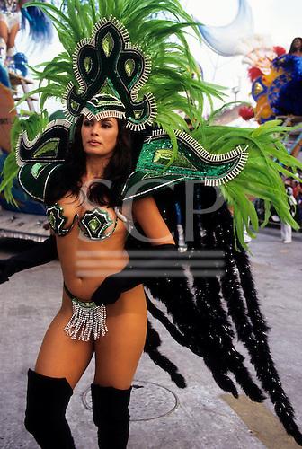Rio de Janeiro, Brazil. Carnival samba school; girl in skimpy dark and light green bikini costume with large feather headdress.
