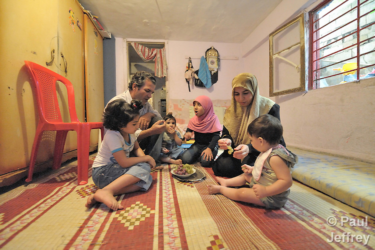 Samina Khafagi (right) feeds her husband Hussein and their four children a snack of grapes in their one-room apartment in Beirut, Lebanon. They are refugees from Iraq, and receive assistance from the Caritas Lebanon Migrant Center, which is funded by Catholic Relief Services, the relief and development agency of the U.S. Catholic community.