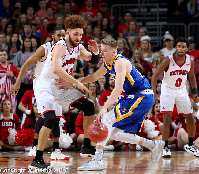 SIOUX FALLS, SD: MARCH 6: 	Trey Burch-Manning #12 from the University of South Dakota applies pressure to Reed Tellinghuisen #23 from South Dakota State University during the Summit League Basketball Championship on March 6, 2017 at the Denny Sanford Premier Center in Sioux Falls, SD. (Photo by Dave Eggen/Inertia)