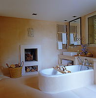 The master bathroom with sand-coloured plaster walls has a recessed fireplace