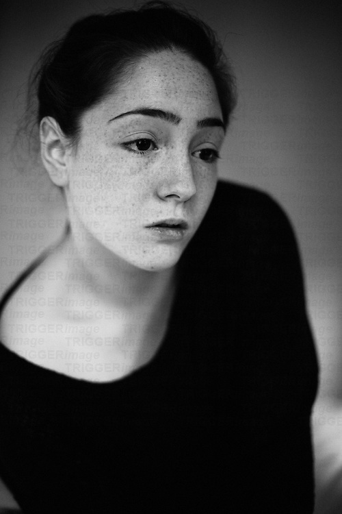 Close up headshot of young woman with sad expression and freckles