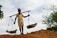 INDIA Jharkhand, Adivasi village Sarwan, farmer carry yoke with  rice plants in baskets for replanting in paddy field / INDIA Jharkand , Adivasi Dorf Sarwan, Bauer mit Tragjoch auf den Schultern, in den Koerben sind Reissetzlinge zum Umpflanzen in ein Reisfeld