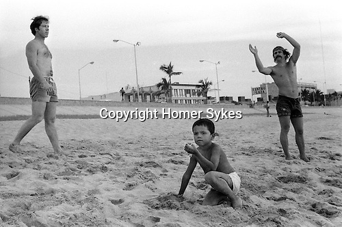 Mazatlan Mexico 1973. Local boy on  beach clutching a tame song bird. American holidaymakers