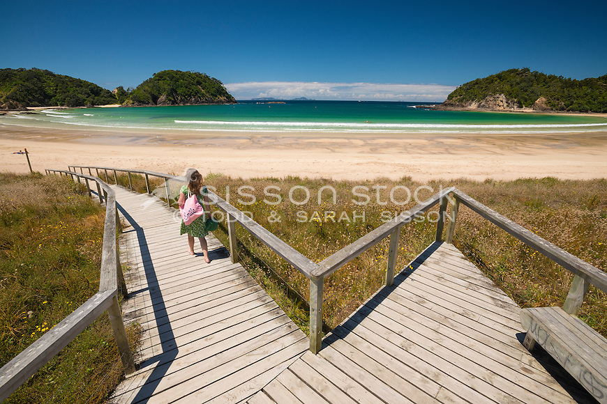 Woman walking down boardwalk to the beach at Matapouri Bay on a summer day,  Tutukaka Coast, Northland, New Zealand - stock photo, canvas, fine art print