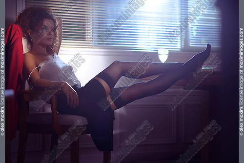 Artistic sensual portrait of a beautiful sexy woman sitting in a chair half undressed in dim night light coming from the window with her legs in stockings on a table