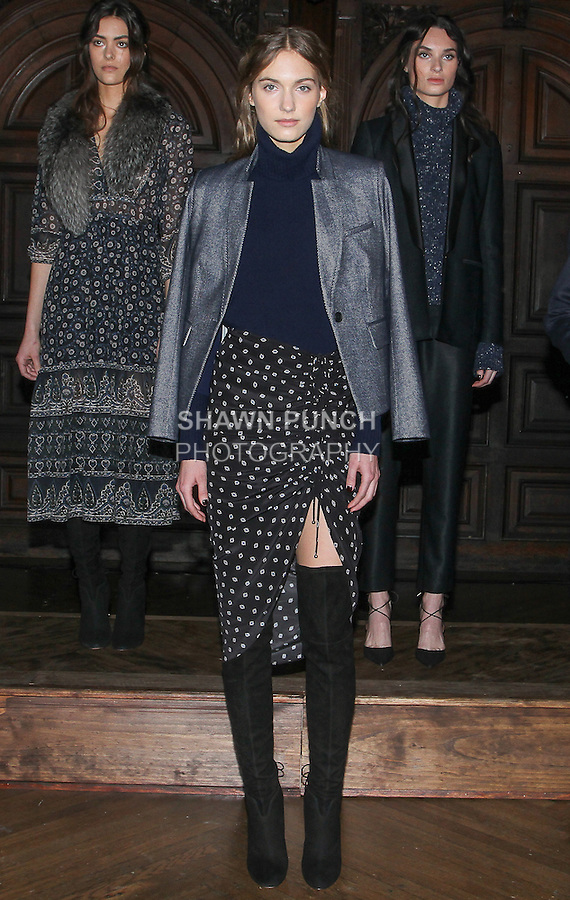 "Model Vera poses in a black deco dot Crepe d Chine ruched drawstring hourglass skirt, navy cashmere mixed weight turtleneck and navy herringbone upcollar schoolboy dickey jacket, from the Veronica Beard Fall 2016 ""Gypsy Caravan"" collection presentation, at the Highline Hotel on February 15 2016, during New York Fashion Week Fall 2016."