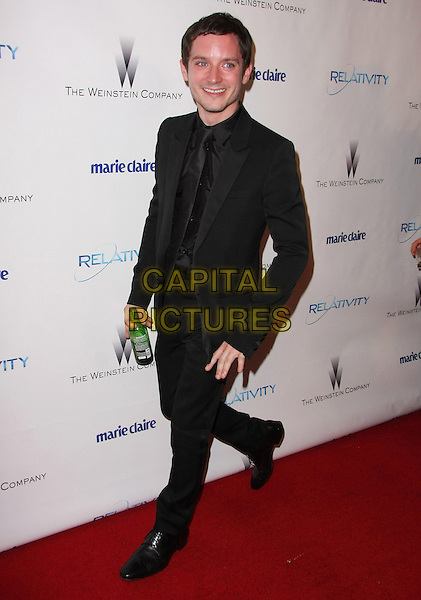 ELIJAH WOOD.Relativity Weinstein Company 68th Annual Golden Globe Awards After Party Presented by Marie Claire held at the Beverly Hilton, Beverly Hills, California, USA..January 16th, 2011.full length black suit walking bottle beer drink beverage .CAP/ADM/TB.©Tommaso Boddi/AdMedia/Capital Pictures.