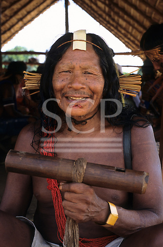 Bacaja village, Amazon, Brazil. Older man holding a wind instrument for the hornets' nest initiation celebration; Xicrin tribe.